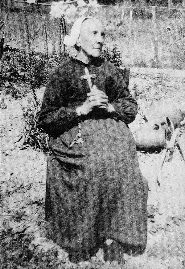 Carte postale de Marie-Julie assise dans son jardin